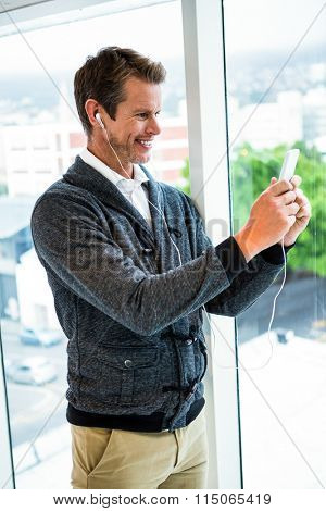 Happy man with headphones using mobile phone against glass window at office