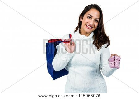 Portrait of happy young woman with shopping bags and footwear against white background