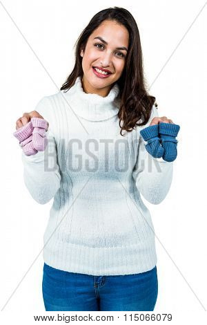 Portrait of happy young woman holding baby shoes against white background