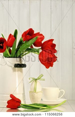 Red tulips and egg with bow on table