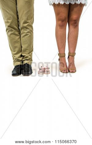 Low section of man and woman amidst baby booties over white background
