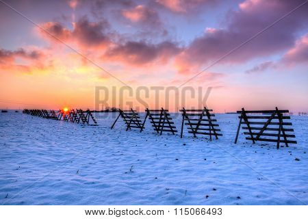 Wooden Snow Blizzard Shields On The Winter Field At Sunset