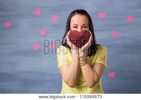 Woman in love holding heart shaped gift box