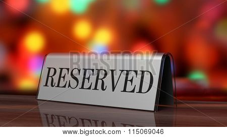 Silver glossy reservation sign on wooden surface, with festive background.