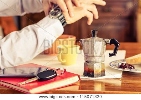 Old Mocha Coffee Machine With Businessman Hands Checking The Time And Breakfast Mugs As Background