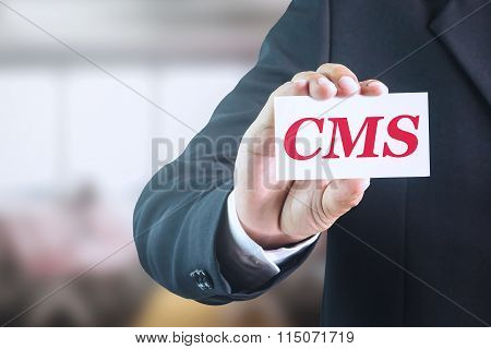 Businessman holding a white sign with the message CMS.