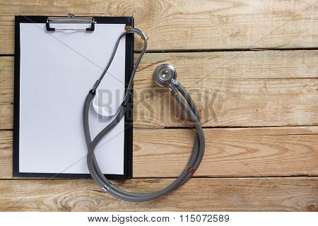 Medical clipboard and stethoscope on wooden desk background. Top view. Workplace of a doctor