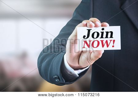 Businessman holding a white sign with the message join now.