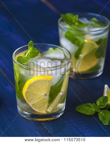 Glasses of lemonade with lemon, lime and mint