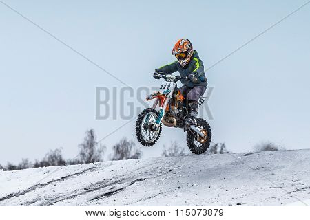 little boy athlete motorcycle jumping over hill on motocross