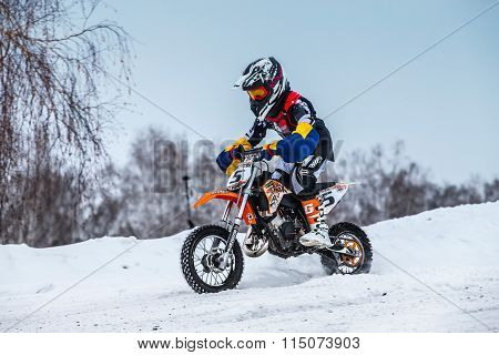 closeup little boy racers motorcycle rides through snow-covered motocross track