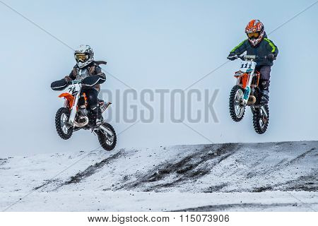 two boys riders motorcycle flying after jumping over mountain