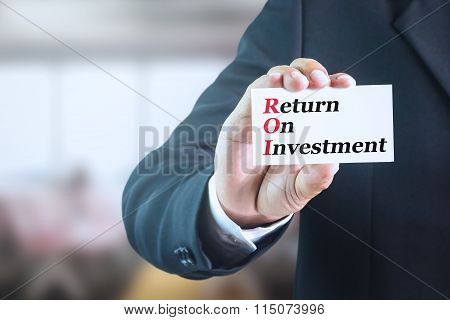 Businessman holding a white sign with the message RETURN ON INVESTMENT (ROI).