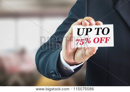 Businessman holding a white sign with the message up to 75% off.