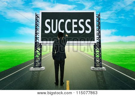 Businessman Standing On Road And Pointing With Large Sign Of Success
