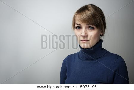 Portrait Of A Beautiful  Girl With Sad Eyes On A Grey Background.