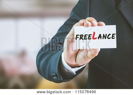 Businessman holding a white sign with the message FREELANCE.