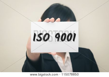 ISO 9001 message on the card Held by women.