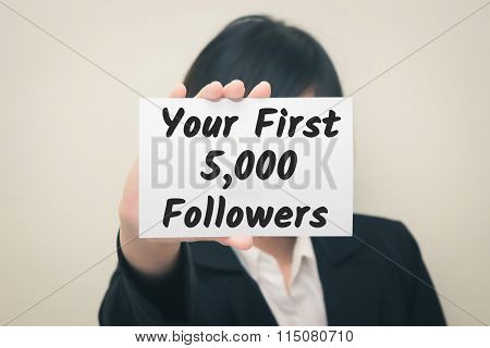 your first 5000 followers message on the card Held by women.
