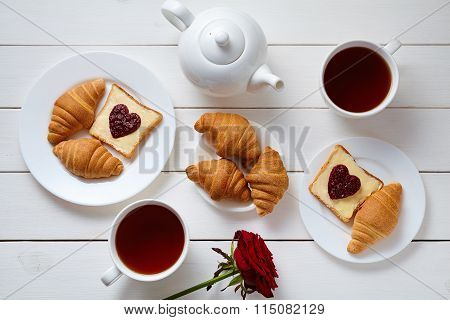 Romantic breakfast for two with toasts, heart shaped jam, croissants, rose and tea on white wooden t