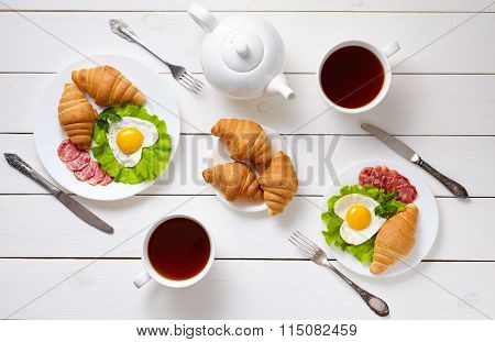 Romantic creative breakfast for two with heart shaped eggs, salad, croissants and black tea on white