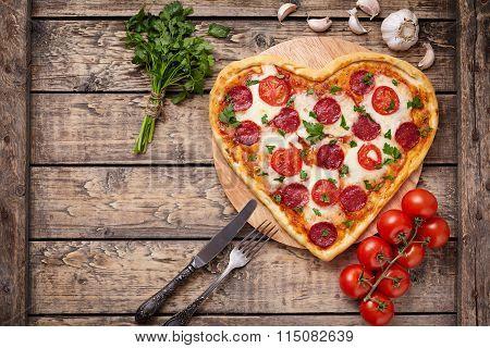 Valentines day heart shaped pizza with pepperoni, cherry tomatoes, mozzarella and parsley on vintage