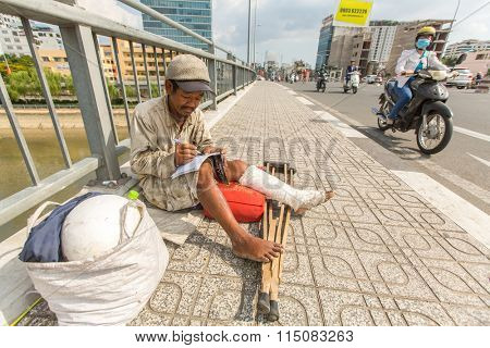 HO CHI MINH, VIETNAM - JAN 14, 2016: Unidentified vietnamese beggar sitting on the street. Located in the South of Vietnam, Ho Chi Minh is the country's largest city, population 8 million.