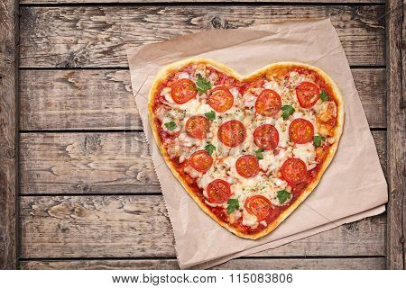 Heart shaped pizza margherita with tomatoes and mozzarella for Valentines Day on vintage wooden back