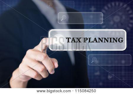 Businessman pressing a TAX PLANNING concept button.
