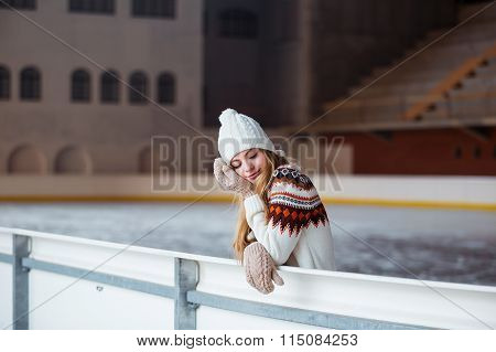 Young woman dressed in a warm woolen cardigan, gloves and hat posing outside at skating park