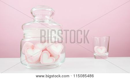 The lovely pink heart marshmallows in small glass jar and shot glass