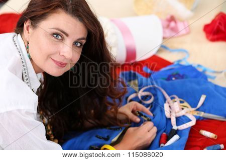 Smiling Female Fashion Designer Sewing Accessories To Retro Style Dress