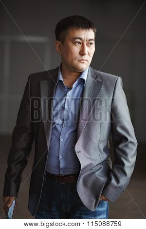 Serious brutal Asian business man with phone in his hands, courageous suit portrait.