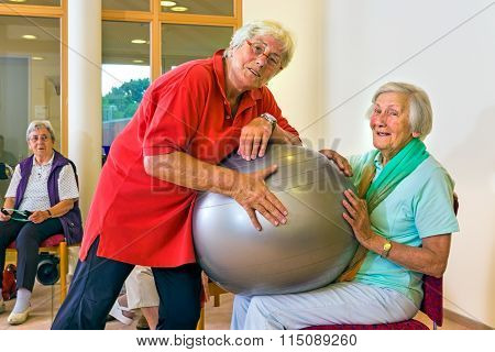 Trainer Helping Woman With Stability Ball