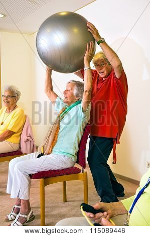 Trainer Helping Woman Lift A Stability Ball