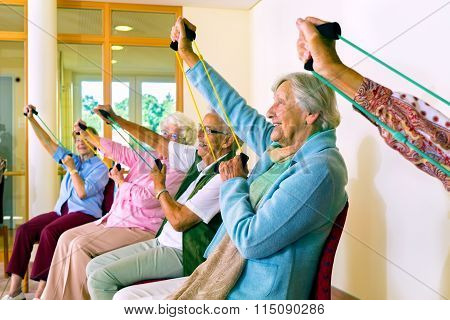Women In Chairs Using Stretching Bands