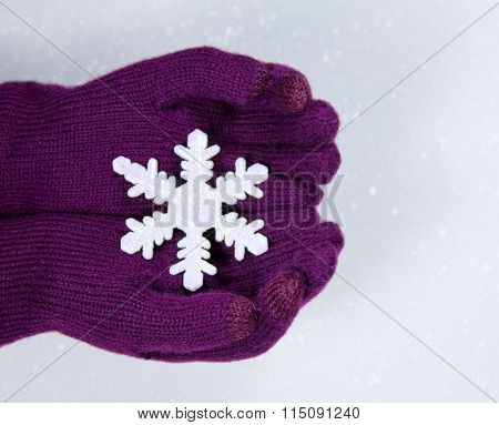 A pair of gloved hands holding a plastic snowflake