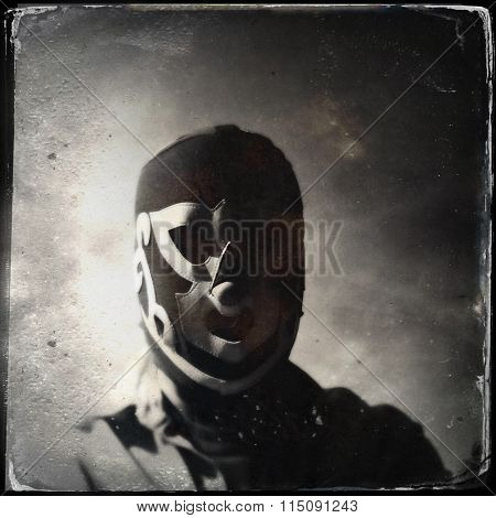 Vintage style portrait of a creepy man in a Mexican wrestling mask - luchador - lucha libre - Instagram tin type filter applied
