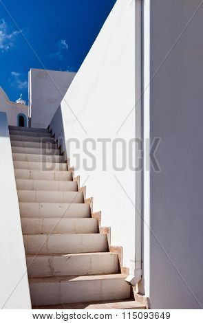 Stairs white walls and a church.