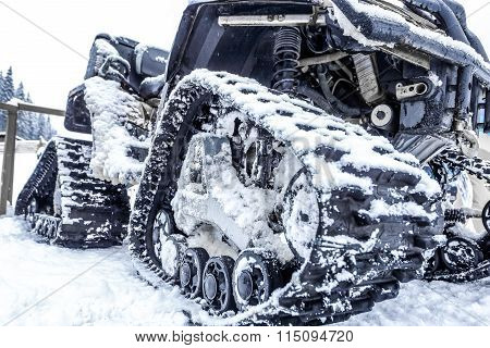 Closeup of a caterpillar snowmobile with snow