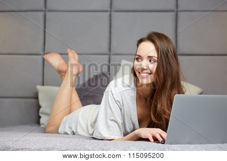 Pretty woman using laptop at home in bedroom