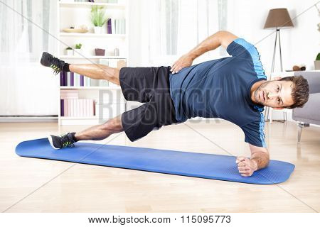 Athletic Man In Side Planking With One Leg Raised