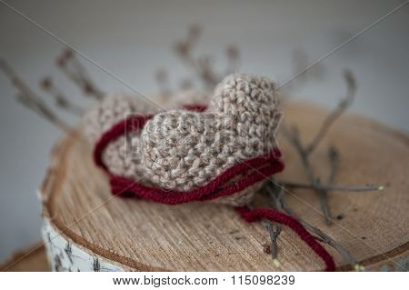 Two Knitting Hearts On Old Wooden Panel.