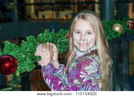Little child girl near Christmas tree.
