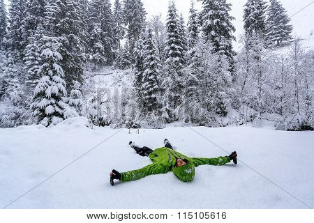 Young boy lying on the snow in forest