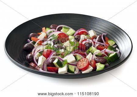 Greek salad on black plate.  Side view, isolated on white with soft shadow.