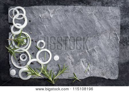 Food background with sliced onions, peppercorns and rosemary on gray slate.  Overhead view.