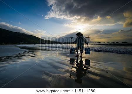 People work in sunrise in My Khe beach, Da Nang, Vietnam.