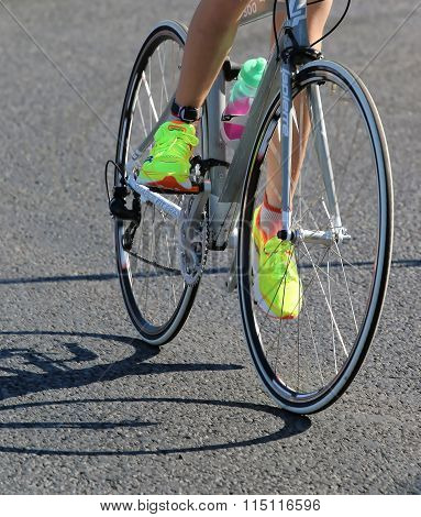 Legs And Feet Of A Cycling Woman With Yellow Shoes In A Triathlon Event
