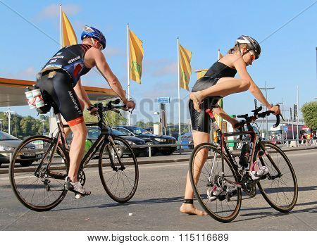 Woman And Man Jumping Up On The Bicycles In The Triathlon Transition Zone